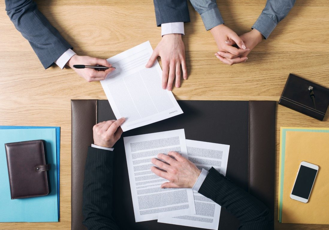 Business man and woman sitting at the lawyers's desk and signing important documents, hands top view, unrecognizable people