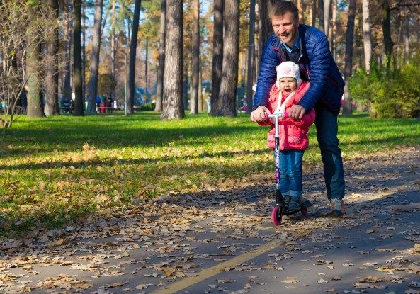 Young Father and Happy Child Riding Kick Scooter in Park with Autumnal Colors of Forest on Background