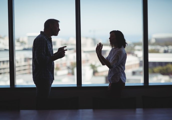 Couple arguing near the window in office